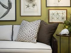 A brown pillow sits under a white and brown patterned pillow on a white sofa with brown piping. Several framed prints of starfish and other aquatic life give the room a nautical quality.