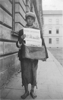 Nowy Sacz, Poland, A Jewish boy selling newspapers in the ghetto, 1940. The ghettos had their own paper they printed. Notice the boy is in rags, thin and dirty. Life in ghettos were terrible, over crowded, lacked food, water, sanitation needs etc