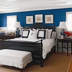 I love this room. In contrast to so many pale color schemes these days, this room really grabs attention with the vibrant blue walls, black bed and crisp white bedding! Not to mention that amazing wood ceiling! Gorgeous!