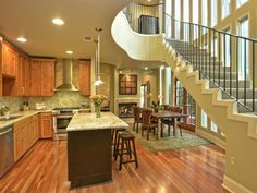 Large kitchen with granite countertops, wood floor and cabinetry with large staircase overlooking the area 705 W Johanna Street B