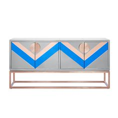 Avant Antique.With a nod to Neo-Memphis style and a wink of Modern American Glamour, consider this the credenza gone cutting edge.Our Nouvelle Credenza features a mirrored case in tones of smoke, cobalt, and copper perched on a minimalist cube base with a mosaic pattern inspired by Pop Art super graphics and Mother Nature's greatest accomplishment—the sunset. Surprisingly versatile, this modern bar looks as good in an industrial loft as it does in a Roman palazzo.Copper etched handles op...