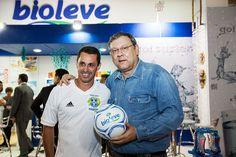 Foto tirada da estande da Bioleve APAS 2012 com Milton Neves segurando uma bola de futebol personalizada e produzida pela Saturno Brindes.