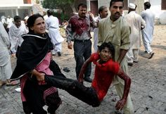 EDS NOTE: GRAPHIC CONTENT - A Pakistani couple help an injured victim of a suicide attack at a church in Peshawar, Pakistan, Sunday, Sept. 2...