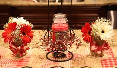 I made the mason jar flower arrangements (they are real gerber daisies and real baby's breath). I decorated the mason jars with burlap and tied red and white burlap ribbon around the center.  I also made the pip berry candle ring that is around the Yankee Candle