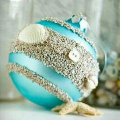 A beachy christmas  Painy strips of glue on an aqua colored bulb in sand and add small shells to detail!