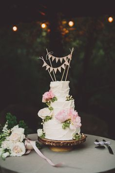 wedding cake with bunting topper - photo by Gina and Ryan Photography http://ruffledblog.com/bohemian-ojai-wedding-at-calliote-canyon