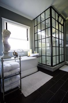 Gorgeous master bathroom boasts a freestanding oval tub and a Pottery Barn Metal Etagere, placed ...