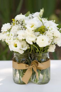 Mason jars are filled with white lisianthus and ranunculus flowers for a rustic feel.