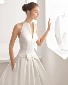 Hay novias que buscan vestidos especiales y este es uno de ellos. Este vestido de novia realizado en otomán, con porte elegante y falda de tablillas, podría ser lo que buscas. El cuerpo halter de escote camisero, le da un punto de modernidad al estilo clásico y aporta un toque de sensualidad.