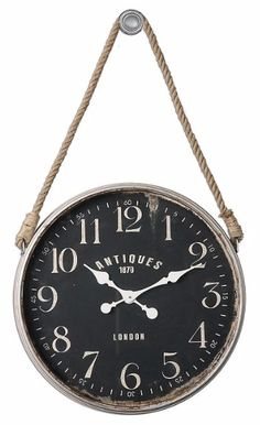 This Bartram clock is loaded with antique appeal. Its aged ivory frame stands out beautifully alongside the matte black clock face. Rust undertones create a distressed feel, and a rope accent allows you to hang the clock from the included hook.