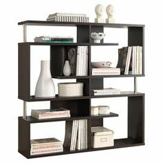 "Bring contemporary appeal to your living room or den with this eye-catching bookcase, showcasing a geometric silhouette and 5 open shelves for displaying framed photos and art books.  Product: BookcaseConstruction Material: Engineered woodColor: Dark brownFeatures:Five shelvesGeometric silhouetteDimensions: 47.25"" H x 47.25"" W x 11.4"" D"
