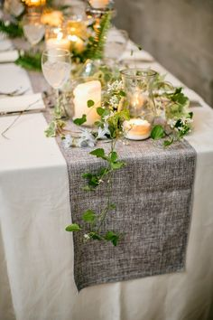 Burlap, clear vases with candles and twisty-viny plants