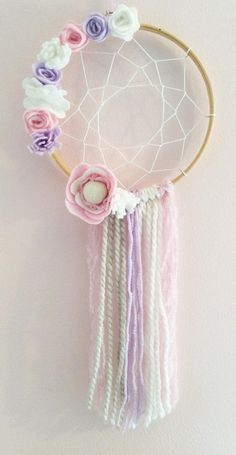 This Floral Bohemian Dream catcher is the perfect decoration for your childs bedroom. It is believed that the carefully woven web inside this dream catcher will catch your bad dreams during the night and allow the good dreams to pass through, float down the tassels and onto you. The