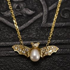 A diamond-encrusted gold bat is suspended from fine golden chains. Her body is a natural pearl, and her eyes glitter fiercely. Originally I made this piece for myself because I've always loved bats. Did you know they're the only mammal that can fly?    Materials: 14k gold, pearl, 12 diamonds (10 x .01ct, 2 x .0025ct = .105ctw).  Age: contemporary. Handmade in NYC.  Size: bat is 11/16