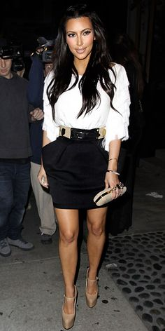 Kim Kardashian in belted tulip skirt and white fringed blouse
