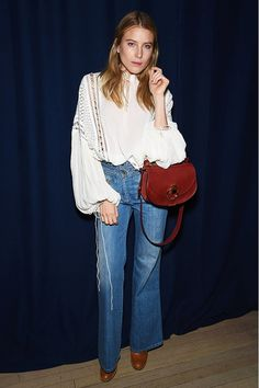 Dree Hemingway wears a '70s-inspired billowy blouse, high-waisted flare jeans, tan leather boots, and a Chloé leather shoulder bag