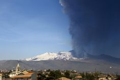 Smoke and ash billow from Mount Etna volcano as the village of Acireale is seen in the foreground, near the Sicilian town of Catania, Italy, Sunday, March 18, 2012.