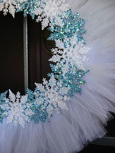 A little inexpensive white tulle and some Dollar Tree glittery snowflakes and... Voila!  Winter wreath! - Use hearts for Valentine's Day