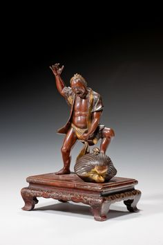 JAPANESE BRONZE FIGURE BY MIYAO A Japanese bronze and parcel-gilt figure by Miyao of a man with his loin cloth trapped in a clam shell, standing on a gold lacquered wooden stand. Signed. Height: 7.25 in / 18.42 cm Width: 5 in / 12.7 cm Depth: 3.75 in / 9.53 cm