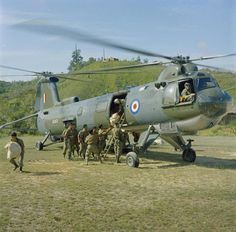 Gurkha troops use a step ladder to climb aboard a Bristol Belvedere twin rotor helicopter of No 66 Squadron RAF at Kuching, British Borneo during operations in Indonesia.