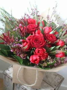 A Valentines bouquet with red Naomi Roses accompanied with seasonal meadow style flowers.