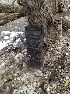 120mm Ammo Can found deep in the woods. The log chain is welded to it and wrapped around a tree, ensuring that it remains at GZ, for future Geocachers to find.