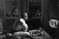 Away from home, a businessman watches TV in a hotel room in 1958. See more photos of Americans, from nuns to presidents, watching TV: http://ti.me/1vvVafR  (Nat Farbman—The LIFE Picture Collection/Getty Images)