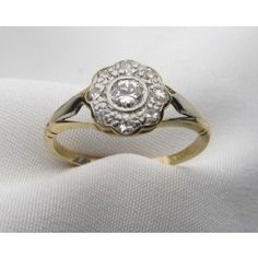 Circa 1910. This sweet Edwardian cluster ring is centered by a bezel set Old European cut diamond and accented by eight small bead set diamonds. The mounting is 18KT yellow gold with platinum accent.