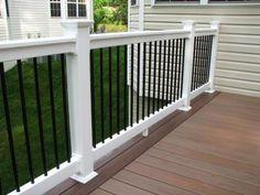 Longevity black aluminum balusters with white PVC #deck railing and WOLF PVC amberwood decking.