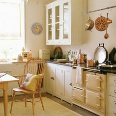 Country kitchen with cream units, wooden table and stone floor | housetohome.co.uk