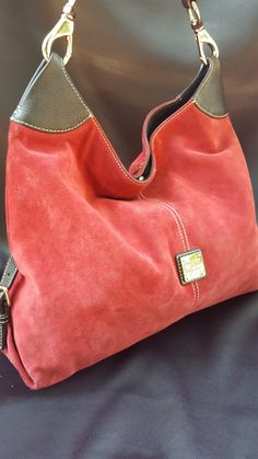 Dooney & Bourke purse with red suede and black leather trim Decorative buckled straps on the ends Silver hardware and center logo Lining is in great shape Gently loved and in great condition with only