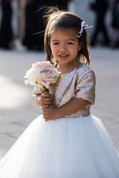 With a sequined top and mini bouquet, this flower girl looks super chic and wedding-ready.