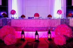 Our clients Hindu Wedding at Playacar Palace, Mexico. Reception Set-up; Head table with staggered floral centerpieces, large pink bouquets and black lanterns for décor.