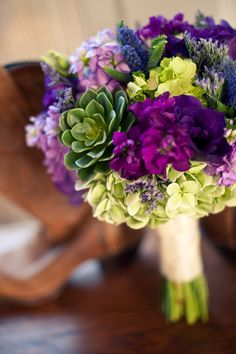 Lovely purples with touches of green including lisianthus, freesia, stock, veronica, hydrangea and rosette succulents.