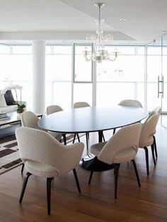 Contemporary dining room with lovely armchair with wood legs and Oval dining Tulip Table. 15 Astounding Oval Dining Table for Your Modern Dining Room ♥ Discover the season's newest designs and inspirations. Visit us at  www.moderndiningtables.net #diningtables #homedecorideas #diningroomideas @ModDiningTables