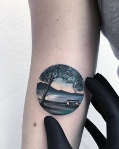 Landscape circle tattoo on the right bicep.