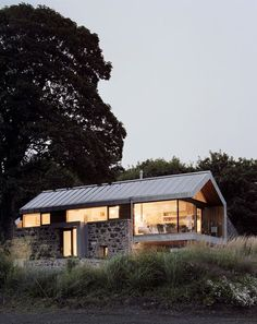 Mix of modern and old. Pitched roof home with stone and glass walls