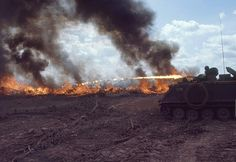 """US soldiers of the 1st squadron 4th Cavalry, on """"Zippo Tracks"""" armored personnel carriers incinerating """"Iron Triangle"""" area, South Vietnam during """"Operation Cedar Falls"""" 1967"""