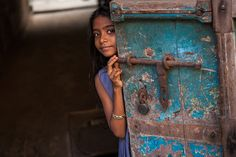 Little girl hiding behind a door in the streets of Kochi (Fort Cochin) in Kerala, India. by Marji Lang via flickr