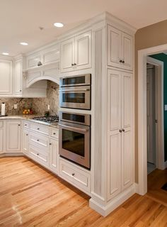 Custom Built Kitchen by Pridecraft. Narrow pantry end cabinets with reeded columns. Cherry Cabinets painted white, with a pewter glaze, and sand through. Inset, beaded face frame doors.