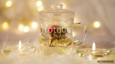 Green chinese tea flower bud blooming in glass tea cup on bokeh background
