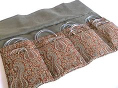 This luxury handmade circular knitting needle case is perfect for organizing all of your needles!    Elegant woven paisley fabric with a complimentary olive green lining in faux suede. Simple cord closure. Twelve individual slots for your needles.    Approximate measurements of case when fully open: 13-3/4 x 14 inches    Measurements when closed: approximately 8-1/4 x 5    Width of individual needle slots ranges from approximately 4 to 5 inches and height of pockets ranges from 3-1&...