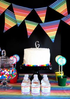 Rainbow Party fabric banner & gumballs around cake base.