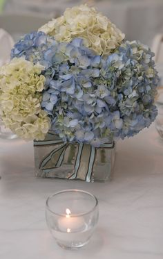 square glass cube of simple hydrangeas, I like the hydrangeas, but I would want more color in the vase or underneath it.