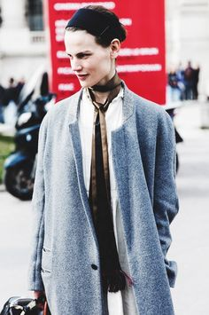 A white shirtdress is paired with a gray coat and skinny scarf