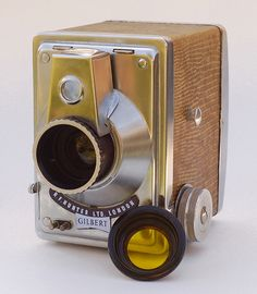 Gilbert.  The Gilbert is a uniquely-styled box camera, made in London by R.F. Hunter Ltd. and introduced in 1953. It's made of stainless steel, with an attractive crocodile covering. Features include a focusing lens, two shutter speeds, two apertures, and double-exposure prevention. It's also got a nice, bright viewfinder that rotates 90° for landscape shots. This example is shown with its original yellow filter, which fits over the lens.