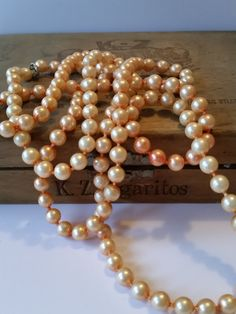 Very pretty vintage 1920s flapper necklace!! This beautiful Great Gatsby style peach faux pearl necklace is extra long, measuring in at 54. The peach faux pearls on this necklace are knotted, making for a very well-made necklace and adding to the illusion of real pearls. This necklace came from my great-grandmothers collection, and I *believe* this is an authentic 1920s flapper necklace as it was in a box with other jewelry from that era, however:  I priced this necklace much lower than the…