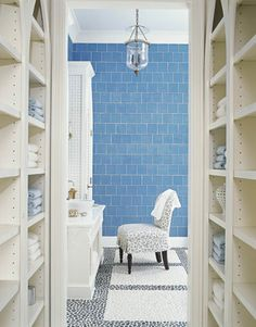 Hallway shelves. The tile, as well as the black and white river stone floor, are from Ann Sacks. A Zoffany print covers a skirted vanity chair found at a consignment shop.