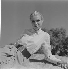 Grace Kelly in a wide cinch belt, full skirting (button down the front)  a classic white blouse....simple yes, and elegant... 1951