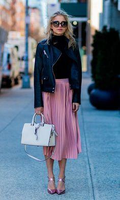Street style look com saia plissada rosa, jaqueta de couro preta, blusa manga longa, bolsa e sapato brancos.